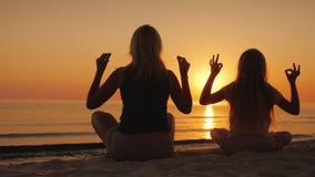 Το Mom και η κόρη θαλασσίως στο ηλιοβασίλεμα Υγεία και ευτυχής χρόνος από κοινού στοκ εικόνες