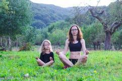 Το Mom και η κόρη κάθονται σε μια θέση λωτού στη φύση Στοκ φωτογραφία με δικαίωμα ελεύθερης χρήσης