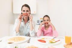 Το Mom και η κόρη κάθονται στην κουζίνα και έχουν το πρόγευμα που έχουν τη διασκέδαση στο πρόγευμα Στοκ εικόνα με δικαίωμα ελεύθερης χρήσης