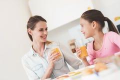 Το Mom και η κόρη κάθονται στην κουζίνα και έχουν το πρόγευμα που έχουν τη διασκέδαση στο πρόγευμα Στοκ φωτογραφία με δικαίωμα ελεύθερης χρήσης