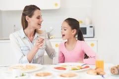 Το Mom και η κόρη κάθονται στην κουζίνα και έχουν το πρόγευμα που έχουν τη διασκέδαση στο πρόγευμα Στοκ εικόνες με δικαίωμα ελεύθερης χρήσης