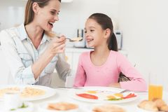 Το Mom και η κόρη κάθονται στην κουζίνα και έχουν το πρόγευμα που έχουν τη διασκέδαση στο πρόγευμα Στοκ Εικόνες