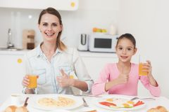 Το Mom και η κόρη κάθονται στην κουζίνα και έχουν το πρόγευμα που έχουν τη διασκέδαση στο πρόγευμα Στοκ Εικόνα