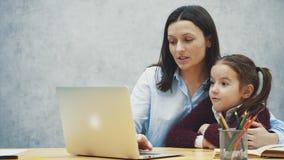 Το Mom και η κόρη κάθονται στον πίνακα Έχετε έναν συμπαθητικό χρόνο μαζί για ένα lap-top Έννοια των σχέσεων απόθεμα βίντεο