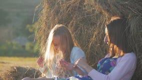 Το Mom και η κόρη κάθονται στο σωρό αχύρου στο ηλιοβασίλεμα Μητέρα και αυτή λίγη κόρη που έχει τον καλό χρόνο στον τομέα υπαίθριο απόθεμα βίντεο