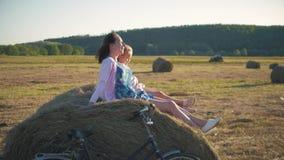 Το Mom και η κόρη κάθονται στο σωρό αχύρου στο ηλιοβασίλεμα Μητέρα και αυτή λίγη κόρη που έχει τον καλό χρόνο στον τομέα υπαίθριο φιλμ μικρού μήκους