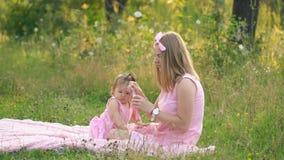 Το Mom και η κόρη κάθονται στο χορτοτάπητα απόθεμα βίντεο