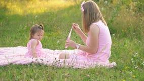 Το Mom και η κόρη κάθονται στο χορτοτάπητα φιλμ μικρού μήκους