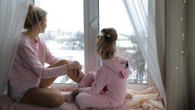 Το Mom και η κόρη κάθονται στο windowsill απόθεμα βίντεο