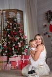 Το Mom και η κόρη κάθονται το χριστουγεννιάτικο δέντρο στοκ εικόνα
