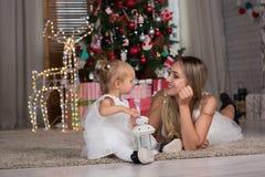 Το Mom και η κόρη κάθονται το χριστουγεννιάτικο δέντρο στοκ εικόνες