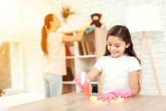 Το Mom και η κόρη καθαρίζουν στο σπίτι Σκουπίστε τα ράφια και τον πίνακα στοκ φωτογραφία με δικαίωμα ελεύθερης χρήσης
