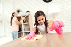 Το Mom και η κόρη καθαρίζουν στο σπίτι Σκουπίστε τα ράφια και τον πίνακα στοκ εικόνα με δικαίωμα ελεύθερης χρήσης