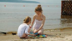 Το Mom και η κόρη παίζουν στην παραλία, χτίζοντας ένα κάστρο άμμου o r απόθεμα βίντεο