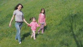 Το Mom και η κόρη περπατούν στο πάρκο Οικογένεια υπαίθρια μια ηλιόλουστη ημέρα Παιδιά με τη μητέρα υπαίθρια το καλοκαίρι απόθεμα βίντεο