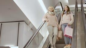 Το Mom και η κόρη πηγαίνουν κάτω από την κυλιόμενη σκάλα απόθεμα βίντεο