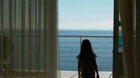 Το Mom και η κόρη πηγαίνουν στο μπαλκόνι με την άποψη θάλασσας από το δωμάτιο φιλοξενουμένων Στοκ Εικόνες