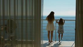 Το Mom και η κόρη πηγαίνουν στο μπαλκόνι με την άποψη θάλασσας από το δωμάτιο φιλοξενουμένων Στοκ εικόνα με δικαίωμα ελεύθερης χρήσης