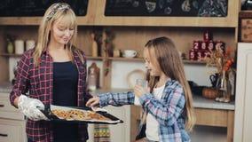 Το Mom και η κόρη σε μια κουζίνα δοκιμάζουν μαζί τα φρέσκα ψημένα μπισκότα σοκολάτας Χριστουγέννων με το γάλα απόθεμα βίντεο