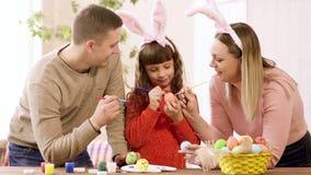 Το Mom και η κόρη στα αυτιά λαγουδάκι και ο μπαμπάς διακοσμούν τα αυγά για τις διακοπές Πάσχας απόθεμα βίντεο