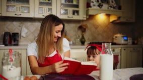 Το Mom και η κόρη στην κουζίνα σε μια κόκκινη ποδιά διαβάζουν το κέικ συνταγής σε ένα σημειωματάριο φιλμ μικρού μήκους