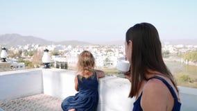 Το Mom και η κόρη στο μπαλκόνι απολαμβάνουν τα όμορφα τοπία της πόλης και των βουνών απόθεμα βίντεο