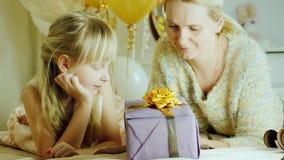 Το Mom και η κόρη συσκευάζουν παρουσιάζουν από κοινού Ευτυχής οικογένεια, δραστηριότητα με ένα παιδί φιλμ μικρού μήκους