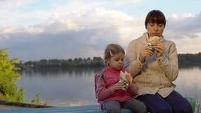 Το Mom και η κόρη τρώνε μαζί doner kebab στην οδό δίπλα στη λίμνη απόθεμα βίντεο
