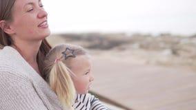 Το Mom και λίγη κόρη κάθονται στην παραλία φιλμ μικρού μήκους