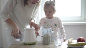 Το Mom και λίγη κόρη προετοιμάζουν ένα milkshake απόθεμα βίντεο