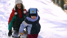 Το Mom και λίγος γιος έχουν το παιχνίδι διασκέδασης στο χιόνι Οδηγούν ένα έλκηθρο φιλμ μικρού μήκους