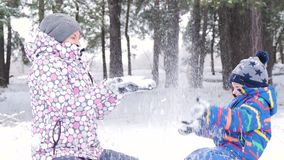 Το Mom και το μικρό παιδί κάθονται στο μεγάλα χιόνι και το παιχνίδι, ρίχνοντας το χιόνι επάνω Η ευτυχή μητέρα και το μωρό στηρίζο απόθεμα βίντεο
