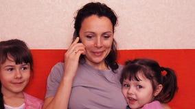 Το Mom και οι κόρες μιλούν στον κινητό Ευτυχής οικογένεια που μιλά στο κινητό τηλέφωνο απόθεμα βίντεο