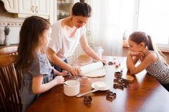 Το Mom και οι κόρες προετοιμάζουν τις ζύμες στη φωτεινή κλασική κουζίνα Δημιουργικός βρωμίστε στον πίνακα Τρόπος ζωής στοκ εικόνες με δικαίωμα ελεύθερης χρήσης