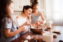 Το Mom και οι κόρες προετοιμάζουν τις ζύμες στη φωτεινή κλασική κουζίνα Δημιουργικός βρωμίστε στον πίνακα Τρόπος ζωής στοκ φωτογραφία με δικαίωμα ελεύθερης χρήσης