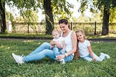 Το Mom και οι κόρες της περπατούν στο θερινό πάρκο στοκ εικόνες
