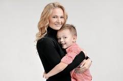 Το Mom και ο γιος αγκαλιάζουν στο απομονωμένο υπόβαθρο Στοκ εικόνες με δικαίωμα ελεύθερης χρήσης