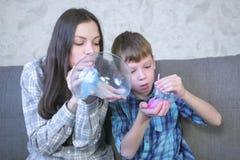 Το Mom και ο γιος διογκώνουν τις μεγάλες φυσαλίδες από slimes Παιχνίδι με slime στοκ φωτογραφία με δικαίωμα ελεύθερης χρήσης