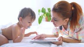 Το Mom και ο γιος εξετάζουν το smartphone στο κρεβάτι απόθεμα βίντεο