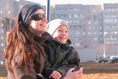 Το Mom και ο γιος κοιτάζουν γύρω, συνεδρίαση γέλιου και συζήτησης σε έναν πάγκο στο πάρκο την άνοιξη Στοκ Φωτογραφίες