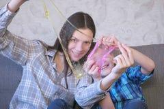 Το Mom και ο γιος παίζουν με slime τη συνεδρίαση στον καναπέ Κοίταγμα μέσω slime στοκ φωτογραφίες