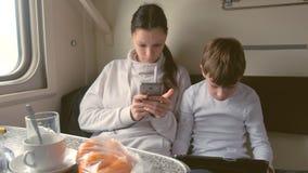 Το Mom και ο γιος στις συσκευές που ταξιδεύουν με το τραίνο παίζουν τα παιχνίδια σε μια δεύτερης θέσης μεταφορά φιλμ μικρού μήκους