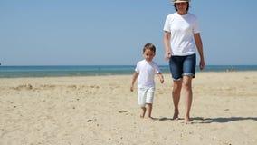 Το Mom και ο γιος της περπατούν κατά μήκος της αμμώδους παραλίας θάλασσας, κρατώντας τα χέρια, προς τη θάλασσα απόθεμα βίντεο