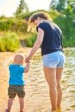 Το Mom και ο γιος της περπατούν κατά μήκος της όχθης ποταμού μια καυτή θερινή ημέρα στοκ φωτογραφίες