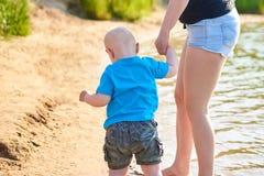 Το Mom και ο γιος της περπατούν κατά μήκος της όχθης ποταμού μια καυτή θερινή ημέρα στοκ εικόνες
