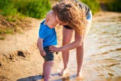 Το Mom και ο γιος της περπατούν κατά μήκος της όχθης ποταμού μια καυτή θερινή ημέρα στοκ εικόνα