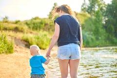 Το Mom και ο γιος της περπατούν κατά μήκος της όχθης ποταμού μια καυτή θερινή ημέρα στοκ εικόνα με δικαίωμα ελεύθερης χρήσης