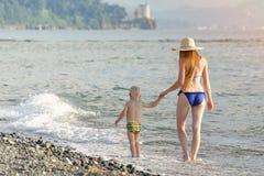 Το Mom και ο μικρός γιος του περπατούν κατά μήκος της άποψης παραλιών από την πλάτη Στοκ Φωτογραφία