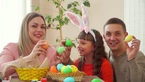 Το Mom και ο μπαμπάς εξετάζουν την κόρη, και παρουσιάζουν έπειτα αυγά Πάσχας στη κάμερα η κόρη μου φορά τα αυτιά κουνελιών απόθεμα βίντεο