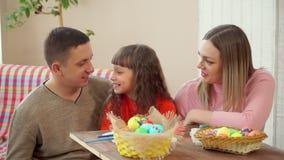 Το Mom και ο μπαμπάς εξετάζουν την κόρη της, και έπειτα ταυτόχρονα παρουσιάζουν αυγά Πάσχας στη κάμερα Στο πρώτο πλάνο είναι α απόθεμα βίντεο